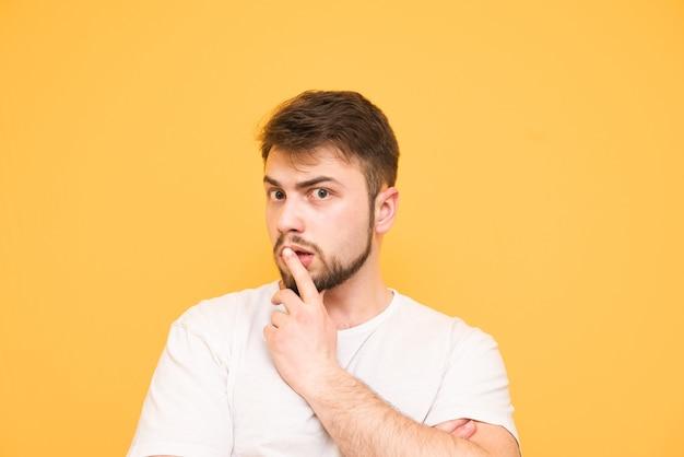 Adolescente in una maglietta bianca su giallo tiene il dito intorno alla bocca e guarda pensieroso la telecamera