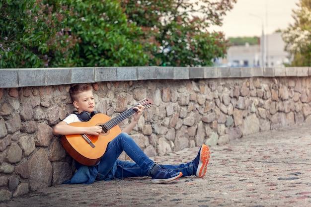 Adolescente con la chitarra acustica e le cuffie che si siedono nel parco.