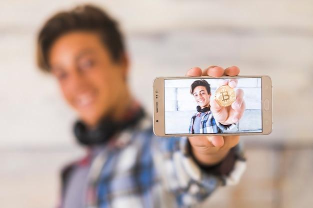 L'adolescente con un grande sorriso e le cuffie mostra la sua foto con un bitcoin in mano