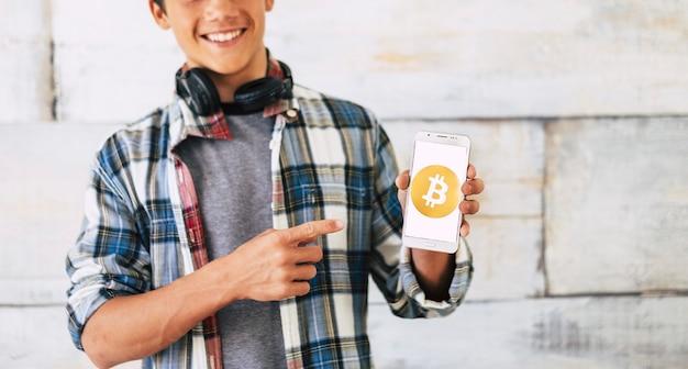 Adolescente con le cuffie in piedi e mostra bitcoin nel suo telefono - è un sorriso