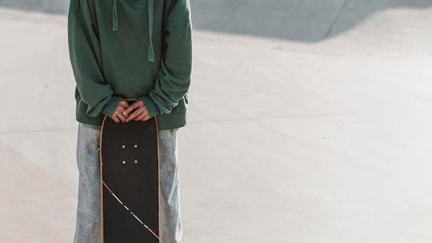 Adolescente con lo skateboard e lo spazio della copia allo skatepark