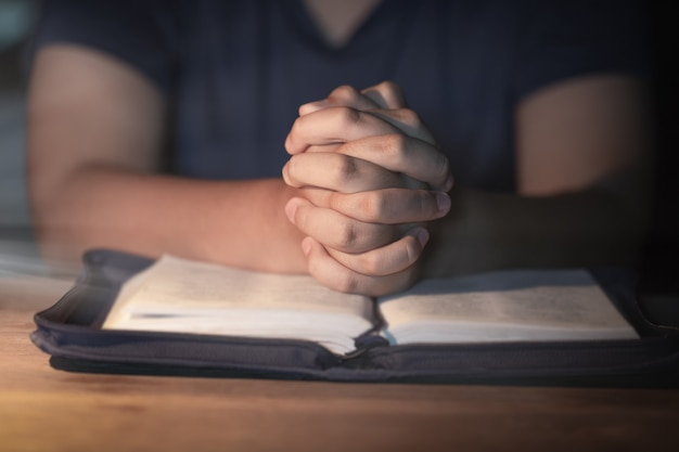 Mano della donna dell'adolescente con la preghiera della croce e della bibbia, mani piegate nella preghiera