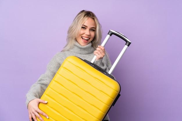 Donna dell'adolescente sopra la parete viola isolata in vacanza che tiene una valigia di corsa come una chitarra