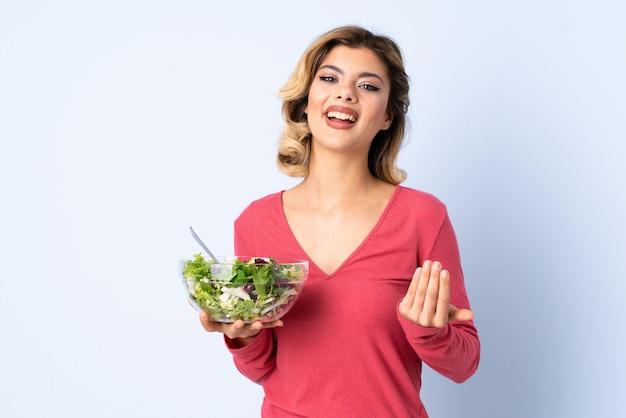 Donna dell'adolescente con insalata isolata sulla parete blu che invita a venire con la mano. felice che tu sia venuto