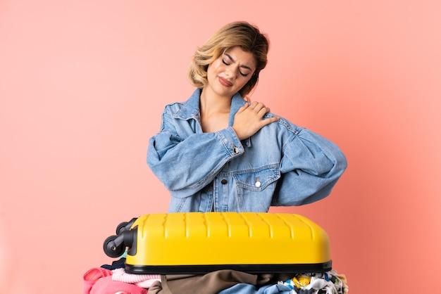Donna dell'adolescente con insalata isolata sul colore rosa che soffre dal dolore alla spalla per aver fatto uno sforzo