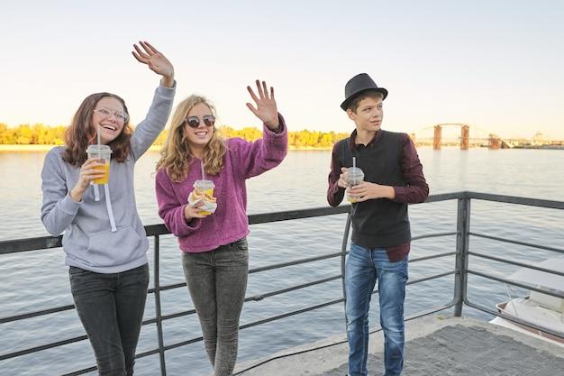 Ragazzo degli adolescenti e due ragazze con la conversazione dell'alimento della via all'aperto
