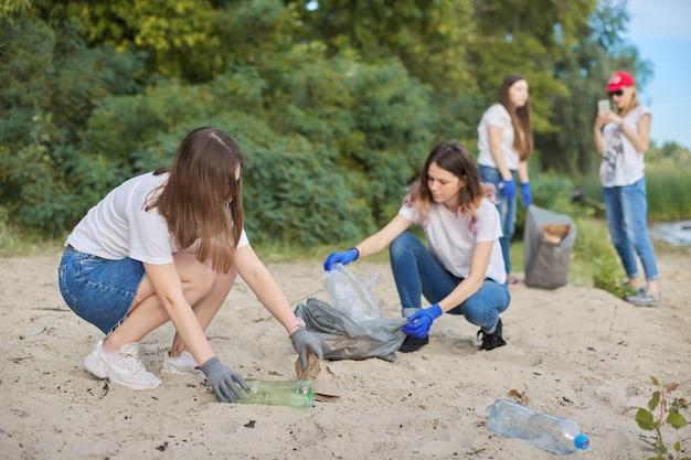 Adolescenti che puliscono i rifiuti di plastica in natura, riverbank