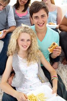 Adolescenti che mangiano hamburger e patatine fritte