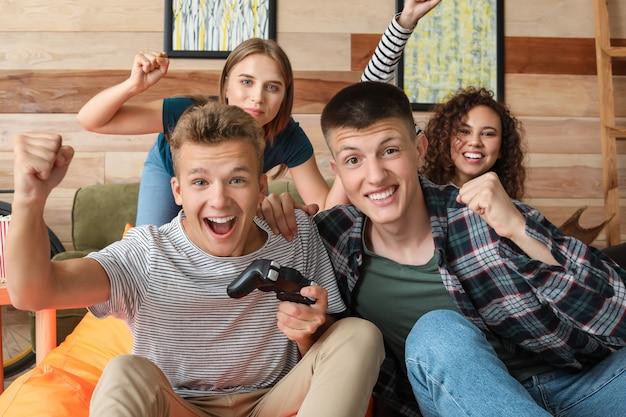 Adolescenti che giocano a videogiochi a casa