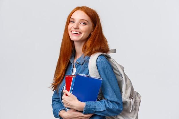 Concetto di adolescenti, studenti e istruzione. studio femminile adorabile allegro della testarossa, andare all'università o all'università, zaino e taccuini spensierati sorridenti della tenuta, bianco diritto