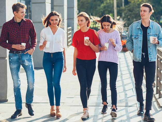 Adolescenti per il tempo libero. divertimento di comunicazione sociale. gruppo di amici femminili maschi che camminano con caffè da asporto.