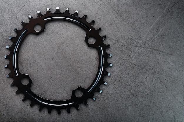 I denti del sistema a stella anteriore della bicicletta su una superficie scura. messa a fuoco selettiva