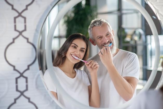 Pulizia dei denti. felice marito e moglie in magliette bianche che riflettono nello specchio lavarsi i denti