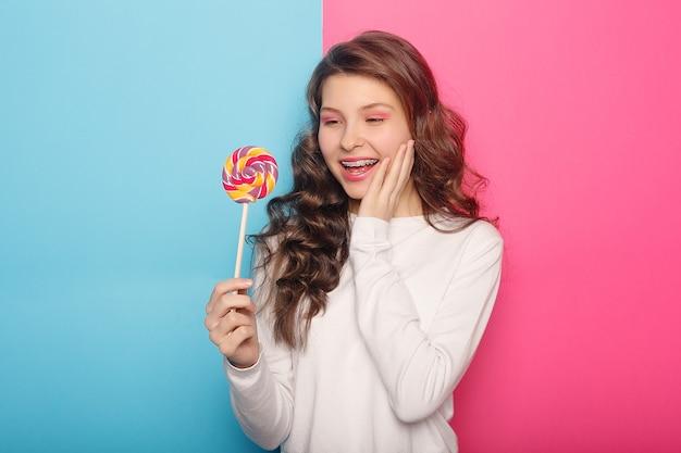 Denti, emozioni, salute, persone, dentista e concetto di stile di vita - donna con bretelle dentali che tengono lecca-lecca. donna dal sorriso sano con parentesi chiare