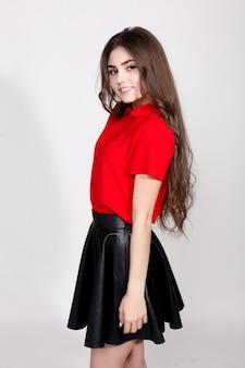 Denti, emozioni, salute, persone e concetto di stile di vita - moda giovane donna bruna in posa indossando gonna di pelle e camicia rossa, guardando la fotocamera.