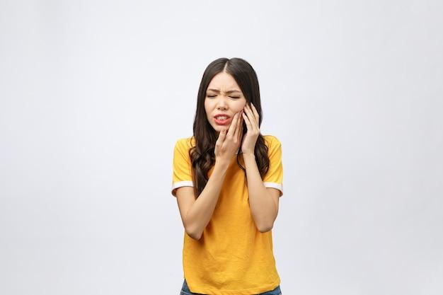 Problema ai denti. sensazione di dolore ai denti della donna. primo piano di bella ragazza triste che soffre di forti dolori ai denti