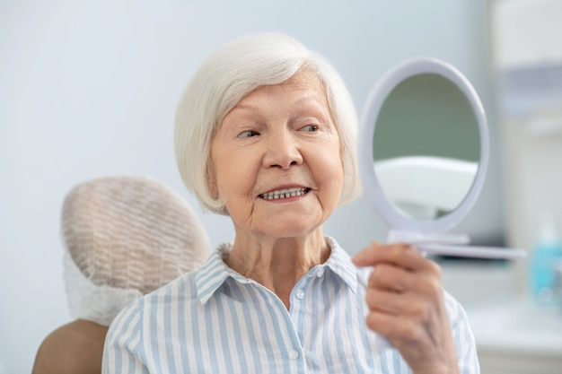 Restauro dei denti. donna anziana che si guarda allo specchio dopo aver visitato l'ufficio dei dentisti