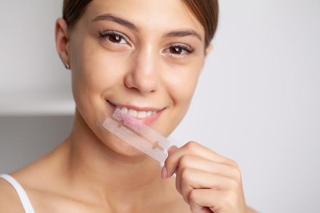 Sbiancamento dei denti, bella donna sorridente che tiene una striscia sbiancante.