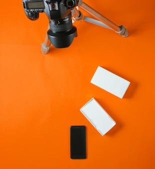 Concetto di tehnobloger. unboxing nuovo smartphone con scatola e recensione con treppiede fotocamera su sfondo arancione. vista dall'alto