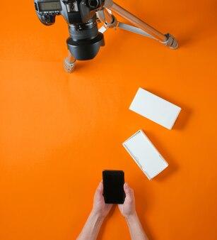 Concetto di tehnobloger. mani delle donne unboxing nuovo smartphone con scatola e blog con fotocamera su treppiede su sfondo arancione. vista dall'alto