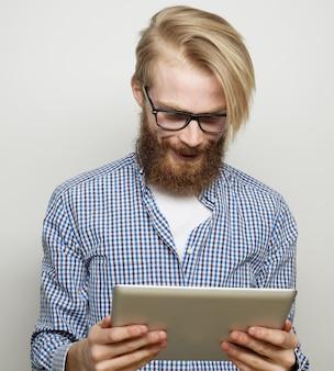 Concetto di tecnologia, istruzione e stile di vita: giovane che utilizza un computer tablet - su sfondo grigio