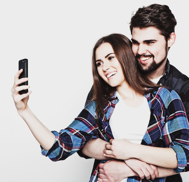 Tecnologia, internet, concetto emotivo e di persone: catturare momenti felici insieme. felice giovane coppia di innamorati che fa selfie e sorride. speciale tonificante alla moda.