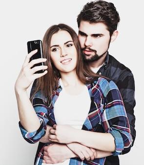 Tecnologia, internet, concetto emotivo e di persone: catturare momenti felici insieme. giovani coppie amorose felici che fanno selfie e sorridono mentre levandosi in piedi contro il fondo bianco.