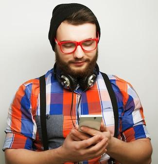Tehnology, internet, emotivo e concetto di persone: giovane uomo barbuto con mobile su sfondo grigio. stile hipster. speciale tonificante alla moda.