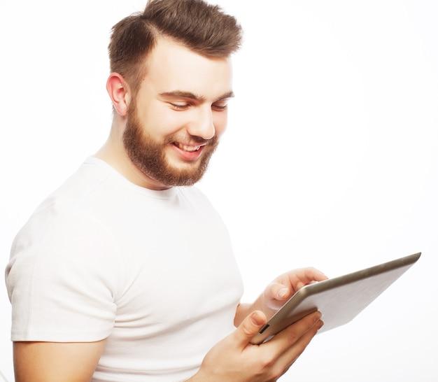 Concetto di tecnologia e stile di vita: giovane che indossa una maglietta bianca utilizzando un tablet - isolato su uno sfondo bianco