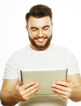 Concetto di tecnologia e stile di vita: giovane uomo che indossa una maglietta bianca utilizzando un computer tablet - isolato su uno sfondo bianco
