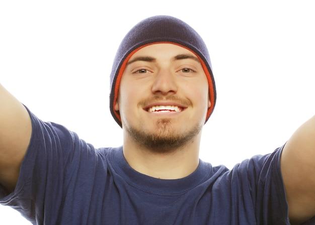 Concetto di tecnologia e persone: selfie felice. bel giovane che tiene la macchina fotografica e fa selfie e sorride.