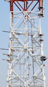 Primo piano della torre delle telecomunicazioni con colore bianco e cielo blu.