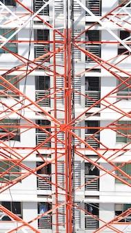 Primo piano della torre delle telecomunicazioni con colore bianco e rosso e cielo blu.