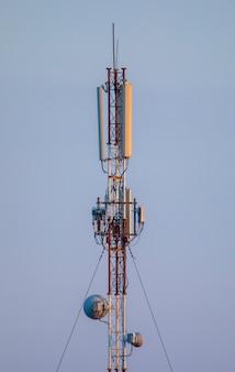 Torre di telecomunicazione 5g per internet e comunicazione mobile su sfondo blu cielo.