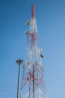 Antenna radio per telecomunicazioni e sfondo del cielo blu della torre satellitare
