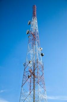 Antenna radio di telecomunicazione e superficie del cielo blu della torre satellitare.