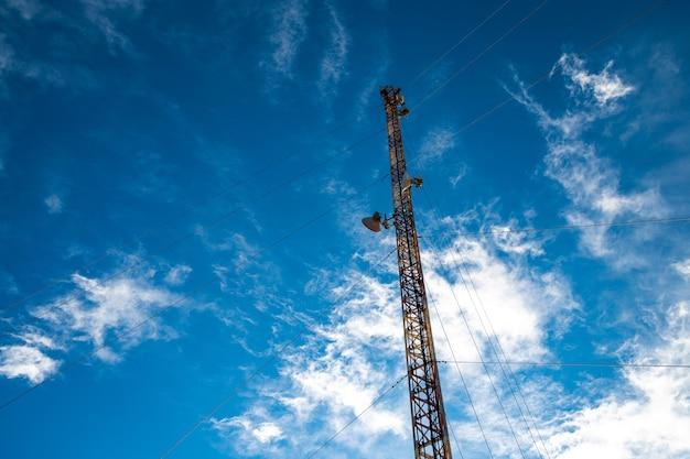Torre delle telecomunicazioni sullo sfondo di un cielo straordinariamente bello con nuvole bianche come la neve sfocate