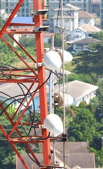 Primo piano della torre di telecomunicazione con colore rosso e bianco.