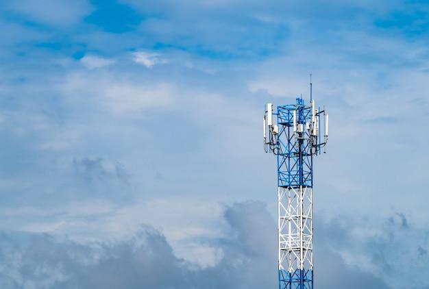 Torretta di telecomunicazione con cielo blu e le nubi bianche