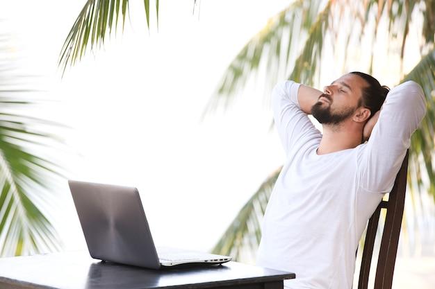 Telelavoro, uomo d'affari che si rilassa sulla spiaggia con laptop e palma, posto di lavoro freelance, lavoro da sogno