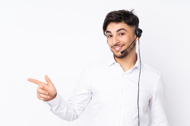 Telemarketer arabian uomo che lavora con un auricolare isolato sul muro bianco che punta il dito a lato