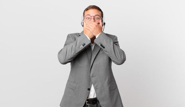Telemarketer uomo d'affari che copre la bocca con le mani con uno shock