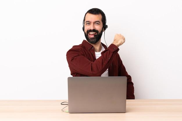 Uomo caucasico telemarketer che lavora con un auricolare e con il computer portatile che celebra una vittoria.