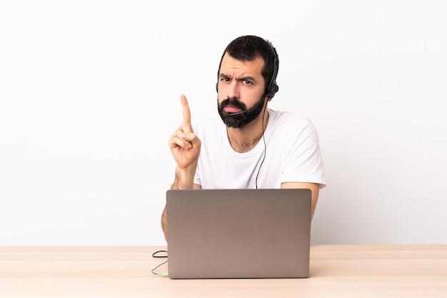 Uomo caucasico telemarketer che lavora con un auricolare e con il computer portatile che conta uno con espressione seria.