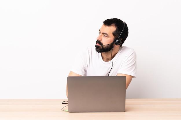 Uomo caucasico telemarketer che lavora con un auricolare e con il laptop tenendo le braccia incrociate