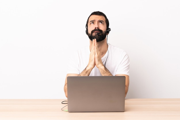 Uomo caucasico telemarketer che lavora con un auricolare e con il computer portatile tiene insieme il palmo. la persona chiede qualcosa.