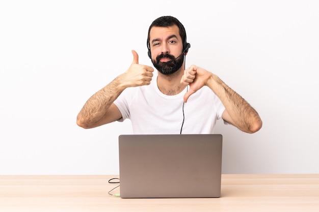 Uomo caucasico telemarketer che lavora con un auricolare e con il computer portatile che fa segno buono-cattivo. indeciso tra sì o no.