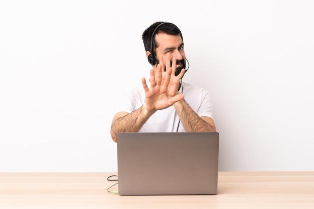 Uomo caucasico telemarketer che lavora con un auricolare e con il computer portatile nervoso che allunga le mani in avanti.