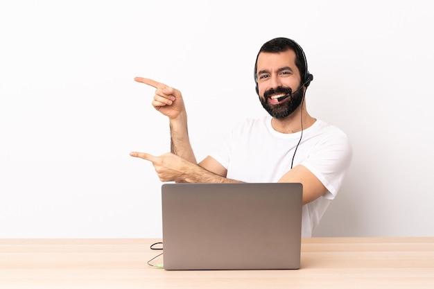Uomo caucasico telemarketer che lavora con un auricolare e con il computer portatile che punta il dito di lato e presenta un prodotto