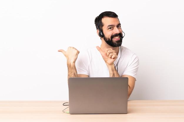 Uomo caucasico di telemarketer che lavora con una cuffia avricolare e con il computer portatile che indica il lato per presentare un prodotto